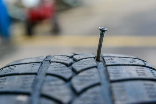 Пробитое гвоздем автомобильное колесо